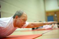 Bilde viser mann som gjør styrkeøvelse for rygg på matte i gymsalen.