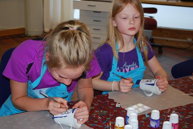 Bilde av jenter som sitter og maler på kopper