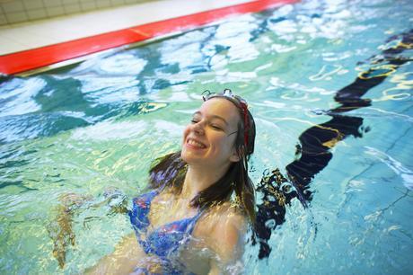 Jente som flyter på ryggen i bassenget.