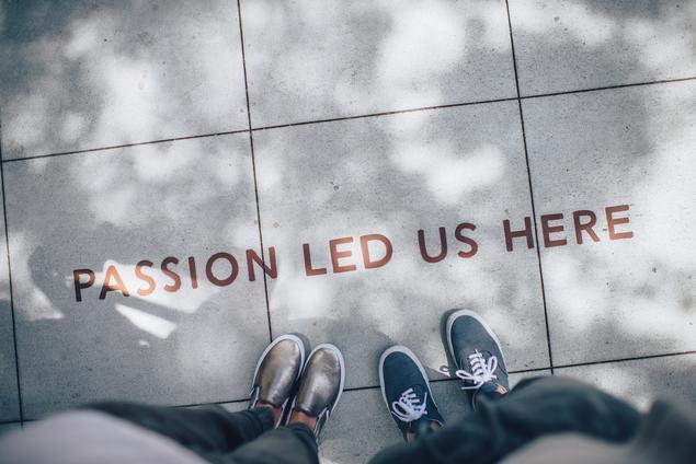 """Bildet viser to sett føtter foran teksten """"passion led us here"""" skrevet på bakken."""
