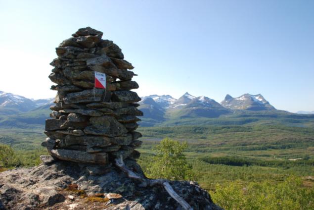 Bilde av varden på Oksskardfjellet med tindene i bakgrunnen.
